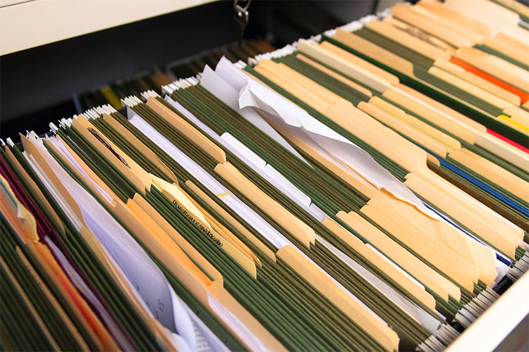 A file cabinet full of messy documents.
